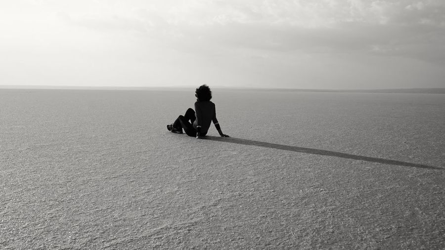 Rear view of woman sitting on salt flat against sky