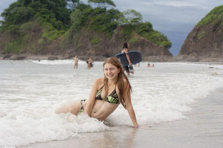 Portrait of happy mid adult woman in bikini sitting on shore