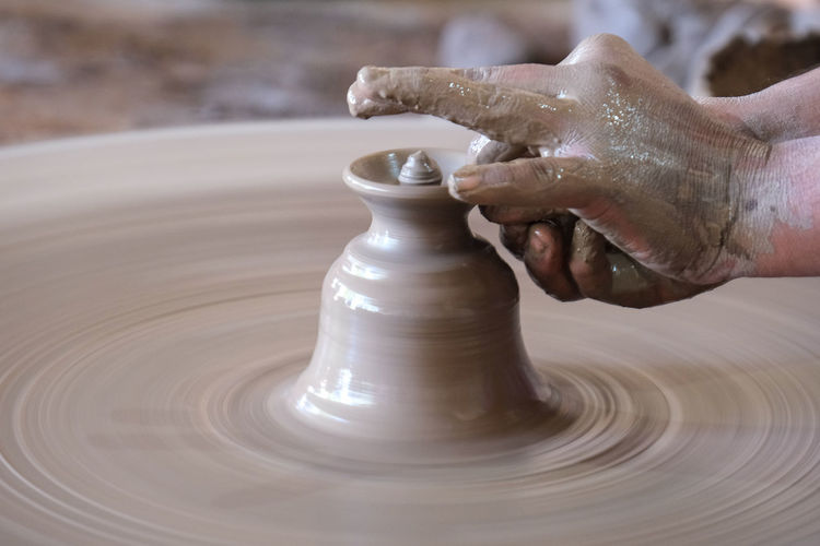Cropped hand of person making pottery at workshop