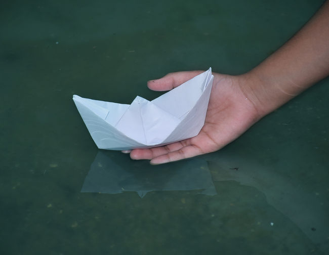 Cropped hand of person holding paper boat in water