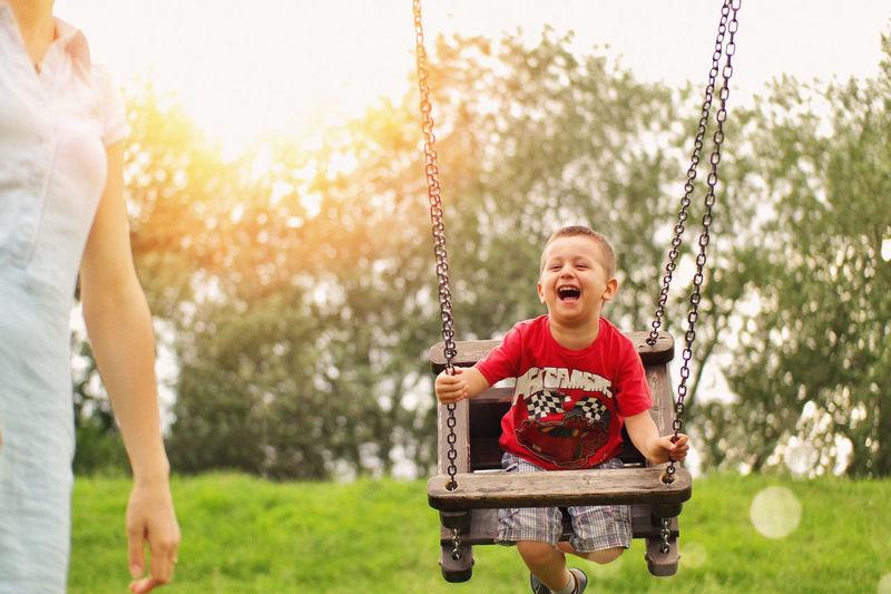 Happy boy holding swing in park