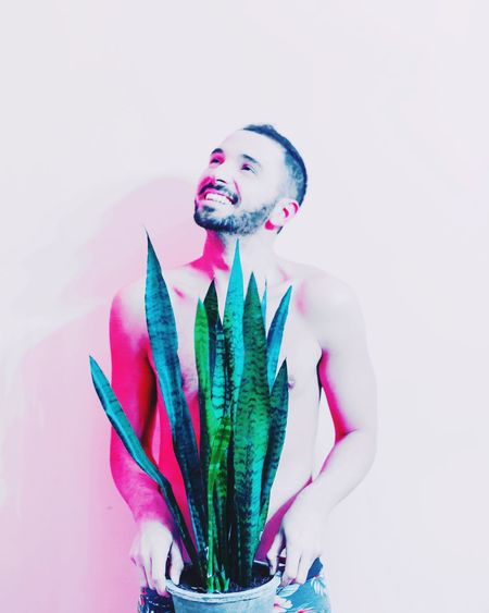 Smiling Shirtless Man Holding Potted Plant Standing Against Pink Background