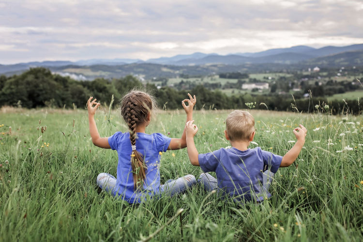 Rear view of children on field