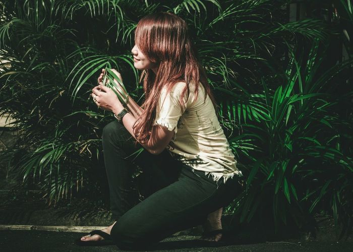 Young woman touching plant