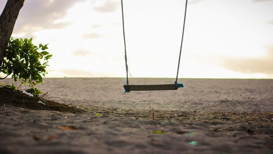Empty swing at playground against sky