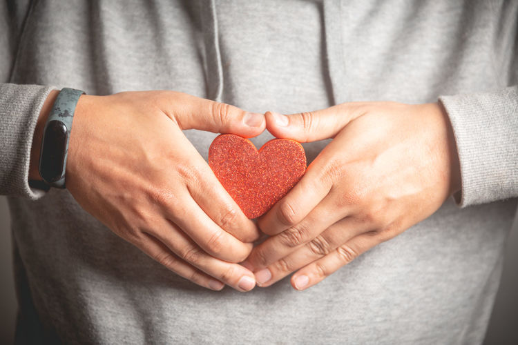 Midsection of man holding heart shape