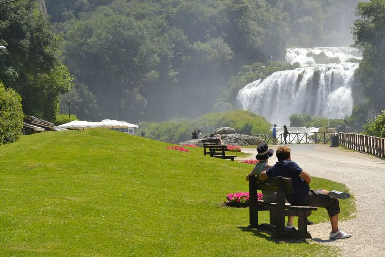 Couple sitting on bench at park against waterfall