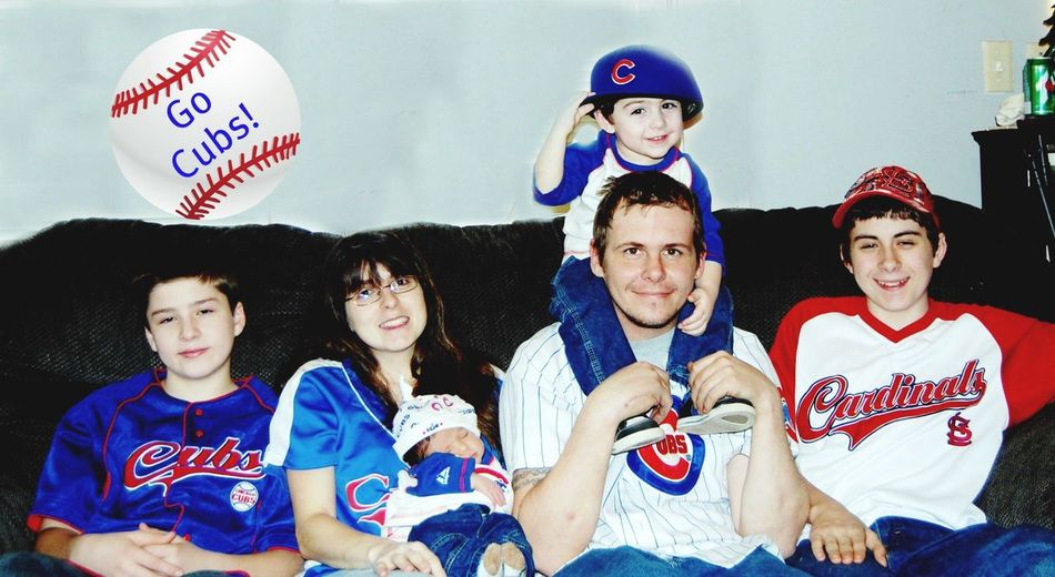 Cubs Family minus 1 Cardinals Fan Cubs Fans Cubs  Group Of People Real People Women Lifestyles Men Front View Togetherness People Celebration Boys Males  Hat Leisure Activity Young Women Indoors  Child Sitting Text Portrait