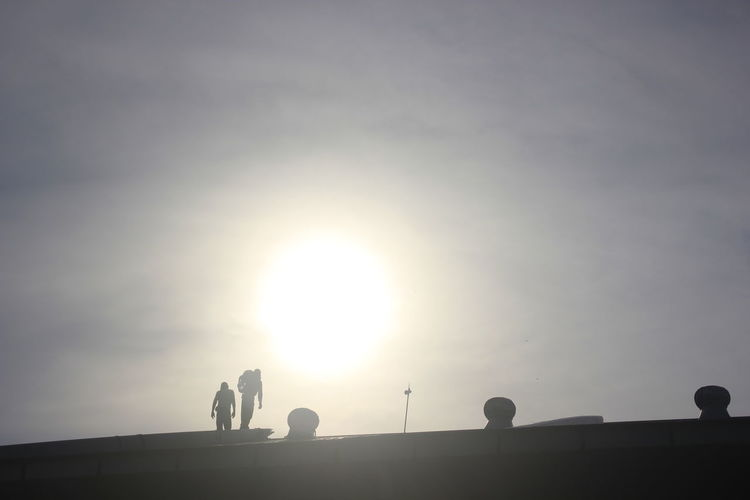 Low angle view of silhouette people against sky during sunset