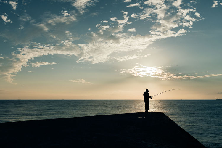 Silhouette man fishing in sea while standing on pier against sky during sunset