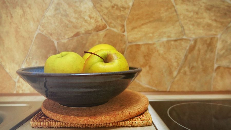 Apples in bowl on table