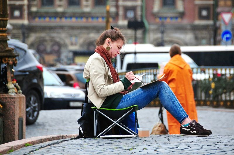Woman painting while sitting on cobbled street in city