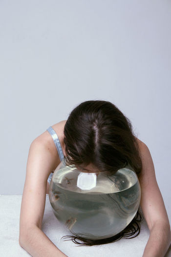 Woman With Fish Bowl On Table Against White Background