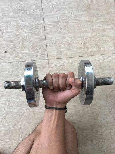 High Angle View Of Man Holding Dumbbell