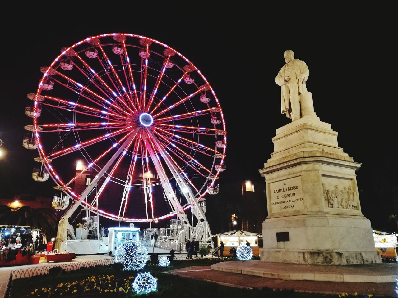 LOW ANGLE VIEW OF ILLUMINATED FERRIS WHEEL IN CITY AT NIGHT