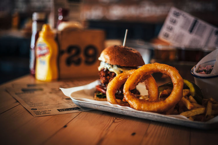 Close-Up Of Burger And Onion Rings On Table