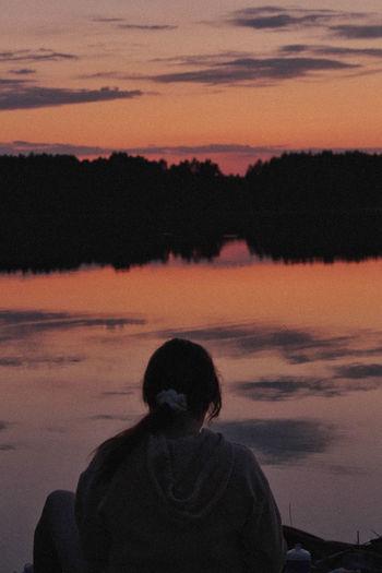 Rear view of silhouette man against orange sky