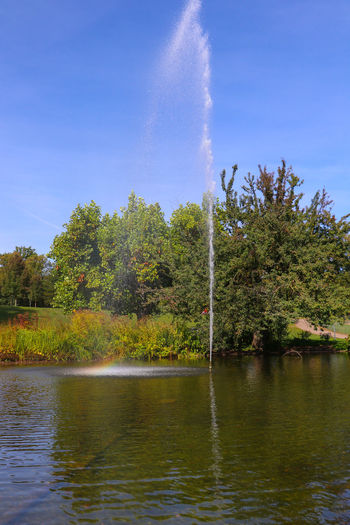 Fountain Tree Water Plant Sky Beauty In Nature Nature Tranquility Lake Scenics - Nature Day Tranquil Scene Growth No People Waterfront Non-urban Scene Forest Outdoors Green Color Vapor Trail Flowing Water Flowing Park - Man Made Space Fountain