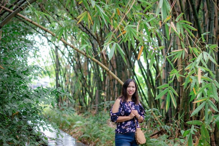Portrait of smiling young woman against bamboo grooves