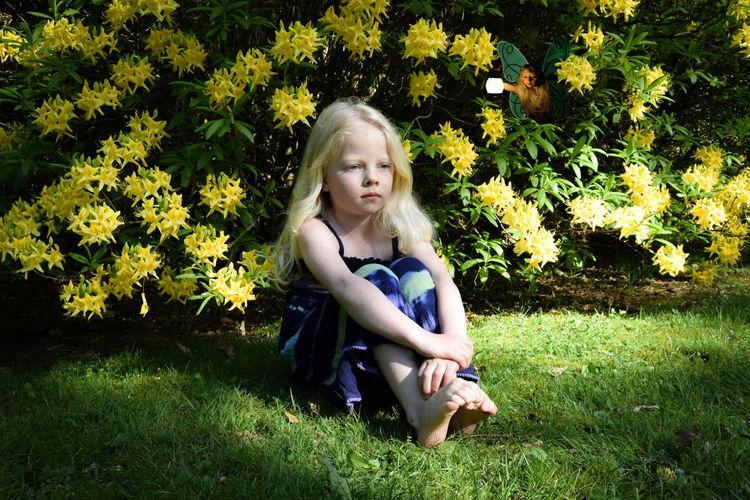 Full length of girl sitting on grassy field at park