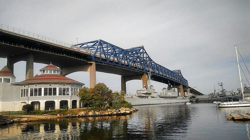 The Charles M. Braga Jr. Memorial Bridge (aka The Braga Bridge). The bridge sits over Battleship Cove, home of the world largest collection of World War II naval vessels. - Bridge Bridge - Man Made Structure Architecture Connection Water River Transportation Waterfront Engineering Outdoors Architectural Column Reflections In The Water Boats Battleships Truss Bridge Truss Angles Shapes And Patterns  Reflections World War Ll Naval Vessel Maritime Museum War Memorial Museum Ship National Historic Landmark