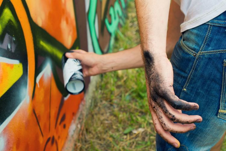 Dirty hand of artist painting graffiti on wall