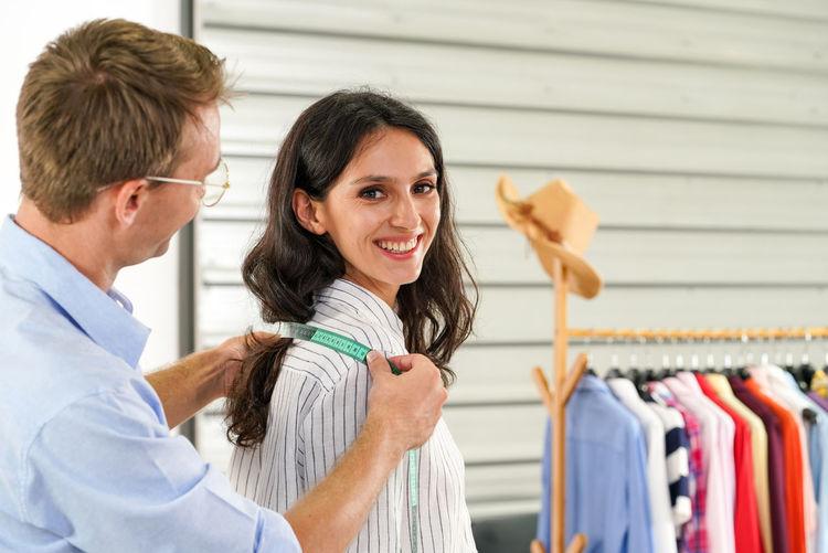 Designer measuring woman shoulder