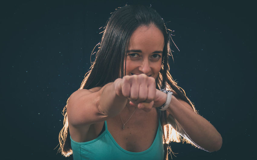Portrait of smiling mid adult woman punching against black background