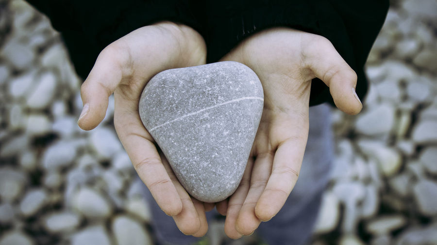 Close-Up Of Human Hands Holding Rock