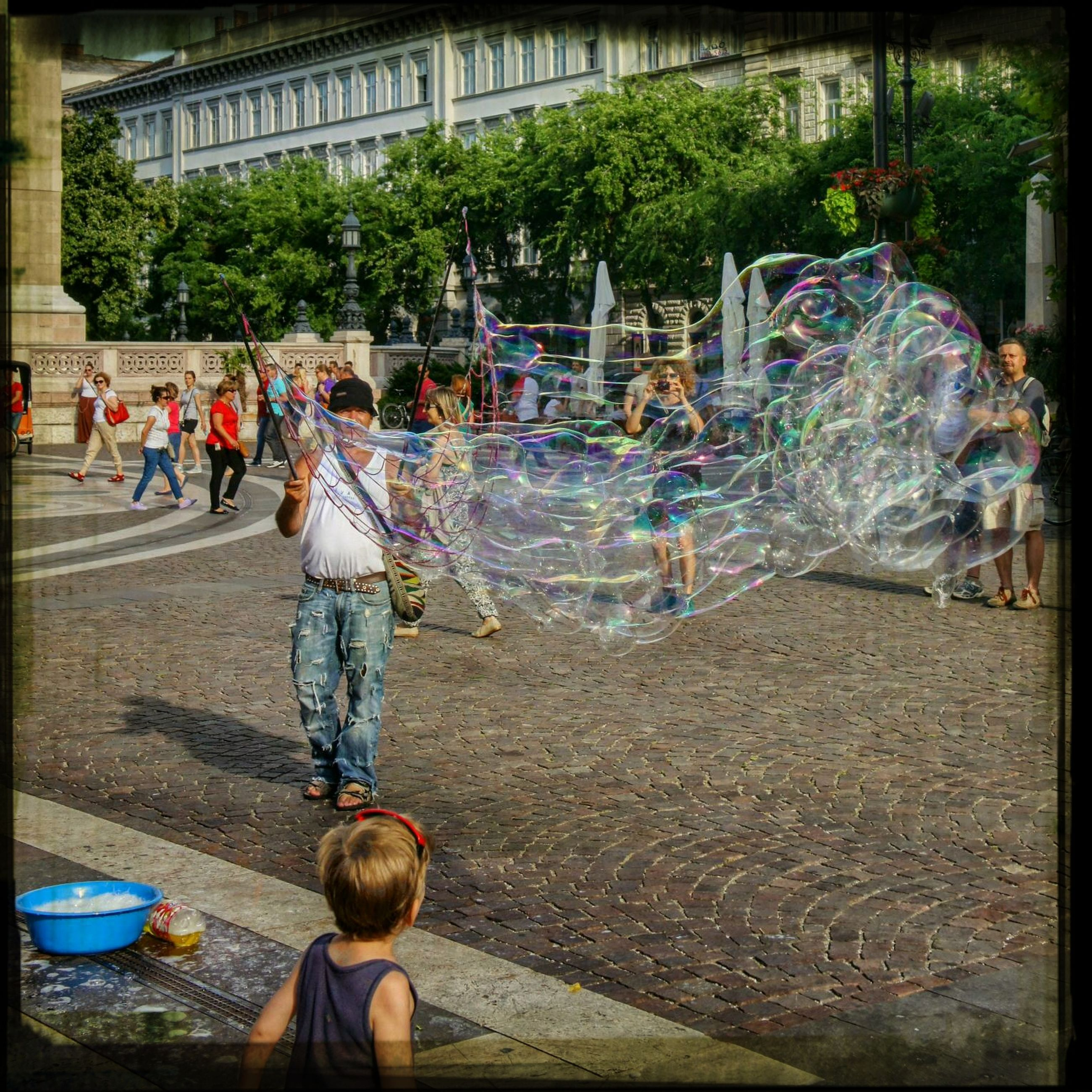 water, incidental people, childhood, lifestyles, leisure activity, fountain, outdoors, auto post production filter, park - man made space, day, transfer print, men, person, large group of people, street, girls, fun, sunlight, enjoyment
