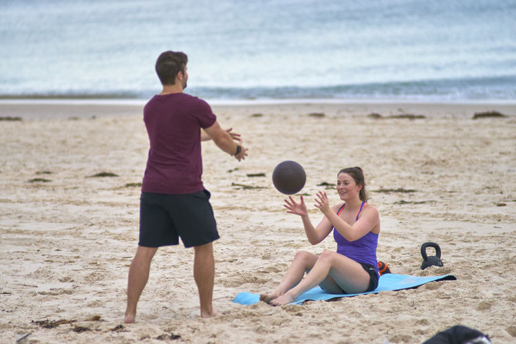 Young Woman Exercising With Fitness Instructor At Beach