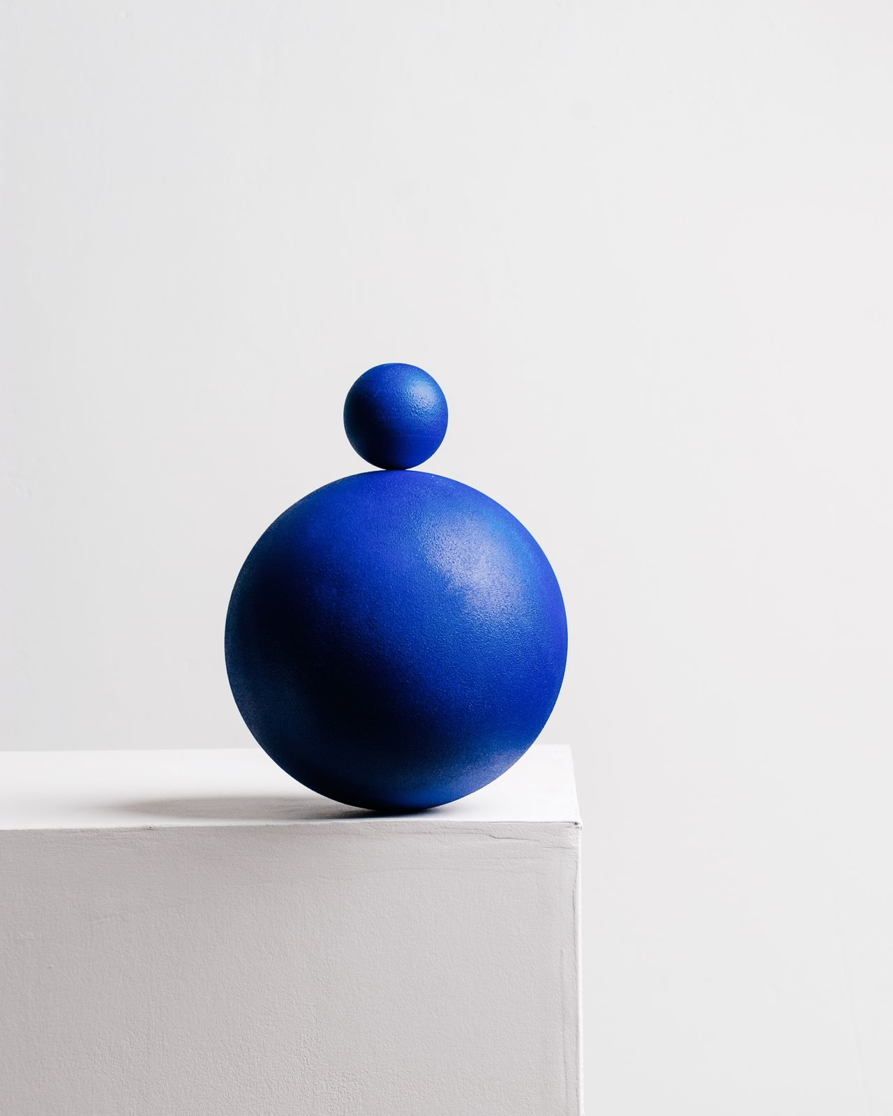 Close-up of blue spheres on table against white wall