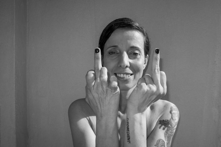 Hipster woman showing middle finger