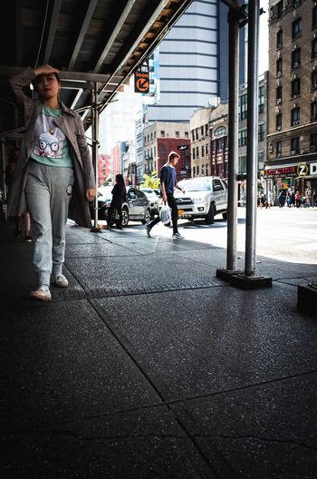 Man walking on footpath by city street