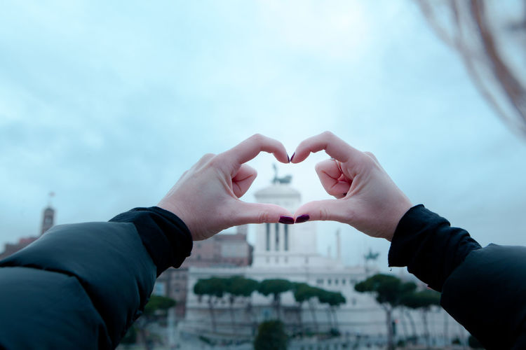 Close-Up Of Hands Holding Heart Shape Against Sky