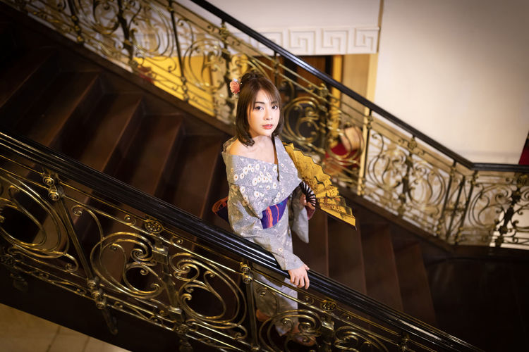 Low angle view of girl looking up on staircase