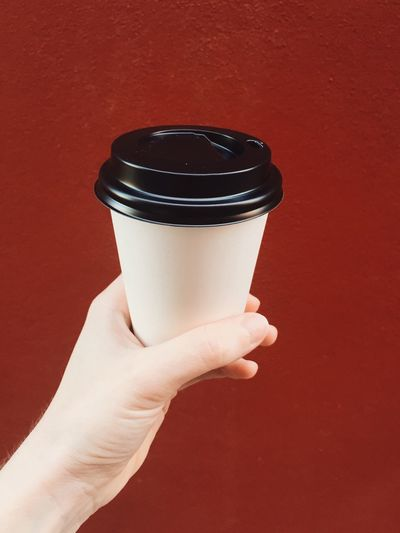 Cropped Hand Of Woman Holding Disposable Cup Against Brown Background