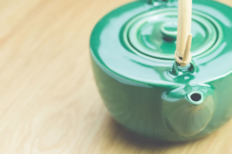 Close-up of green teapot on wooden table at home