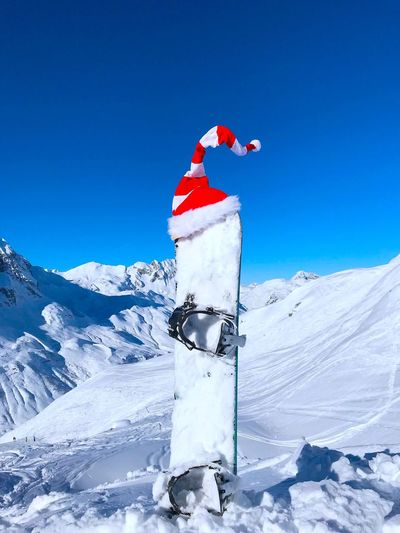 Santa hat on equipment at snowcapped mountain against clear blue sky