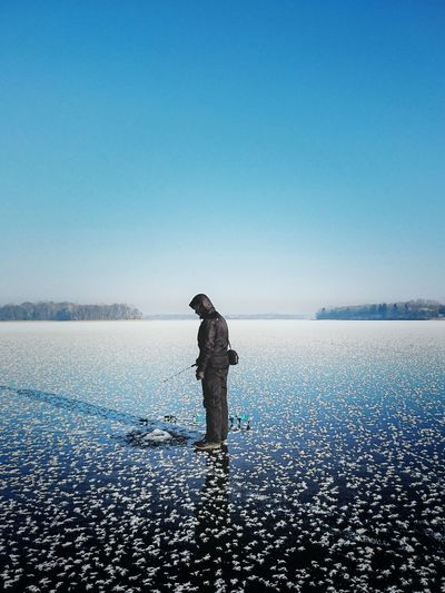 Full length of man fishing in frozen lake