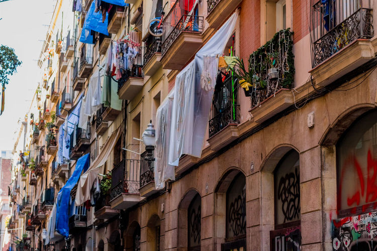 Building Exterior Architecture Built Structure Low Angle View Outdoors No People Day City Clothline Snapshots Of Life Barcelona Portrait Of A City People Occupation Tender Clothes El Raval Raval Neighborhood Classic City Street People Watching Living Lifestyles Cultures