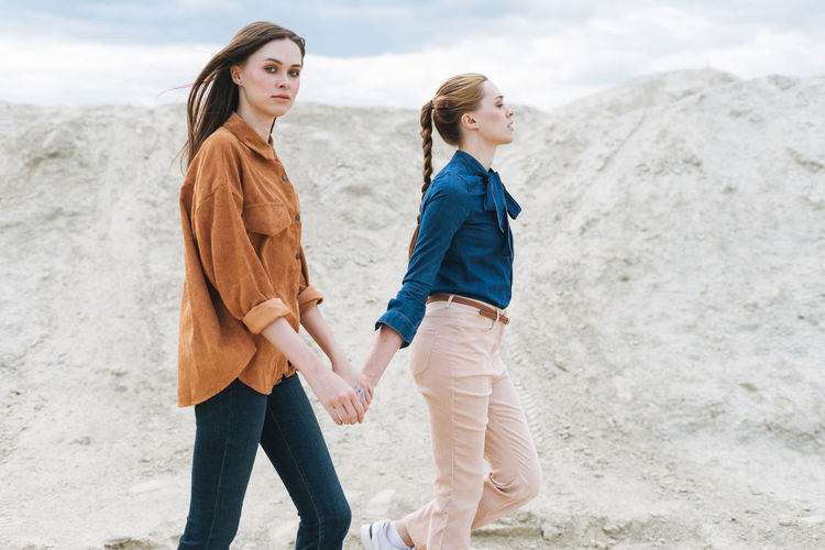 Full length of mother and daughter walking on beach