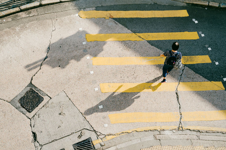 High angle view of man crossing sign on road