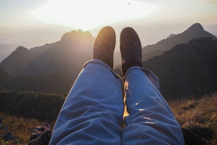 Low section of person relaxing on land against mountains during sunset