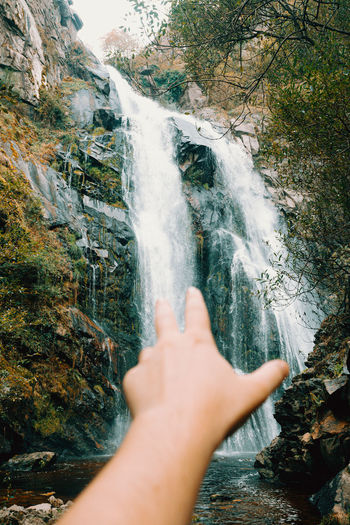 Cropped image of person hand against waterfall