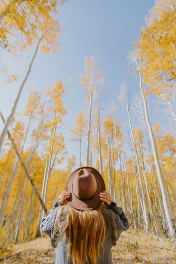 Low angle view of woman standing by trees against sky