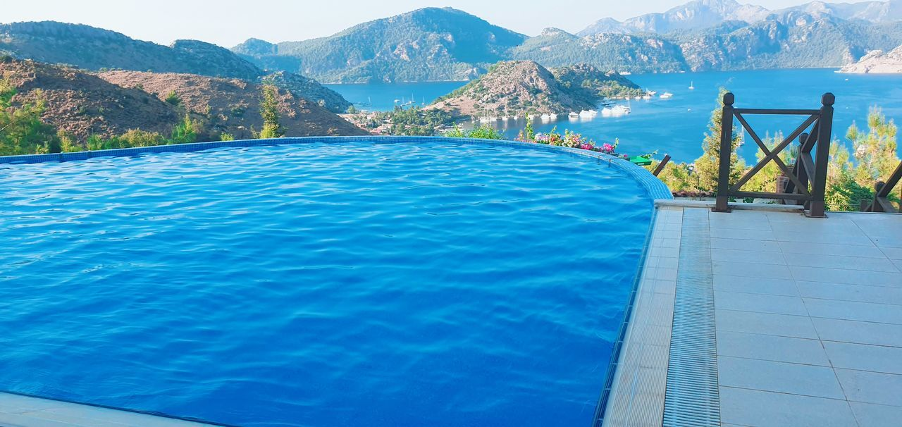 water, swimming pool, pool, mountain, nature, beauty in nature, day, scenics - nature, blue, no people, mountain range, tranquility, turquoise colored, tranquil scene, waterfront, sea, infinity pool, outdoors, idyllic, luxury