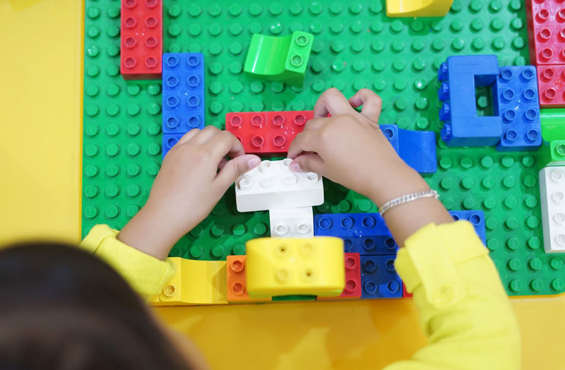 Close up shot of kid's hand playing colorful block game view from top. Brain Game Growth Kids LEGO Playtime Skill  Block Block Shape Childhood Duplo Education Holding Indoors  Kid Multi Colored One Person Parent Parenting Playing Skill Develope