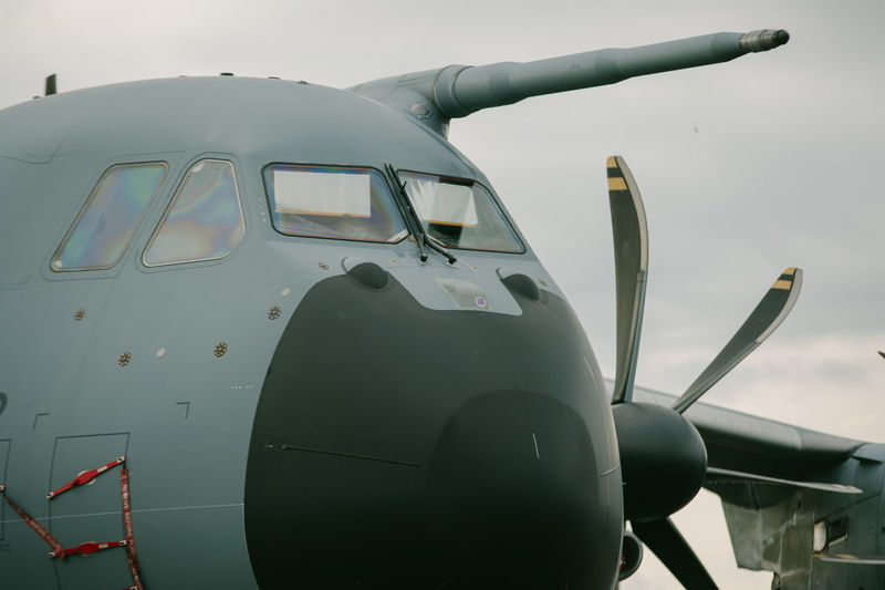 Close-up of airplane on airport runway against sky
