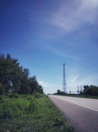Road amidst field against the blue sky and communication tower